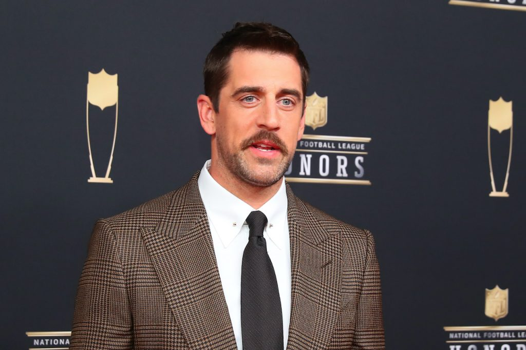 Green Bay Packers QB Aaron Rodgers poses in a brown suit for photos on the red carpet at the NFL Honors at the Fox Theatre
