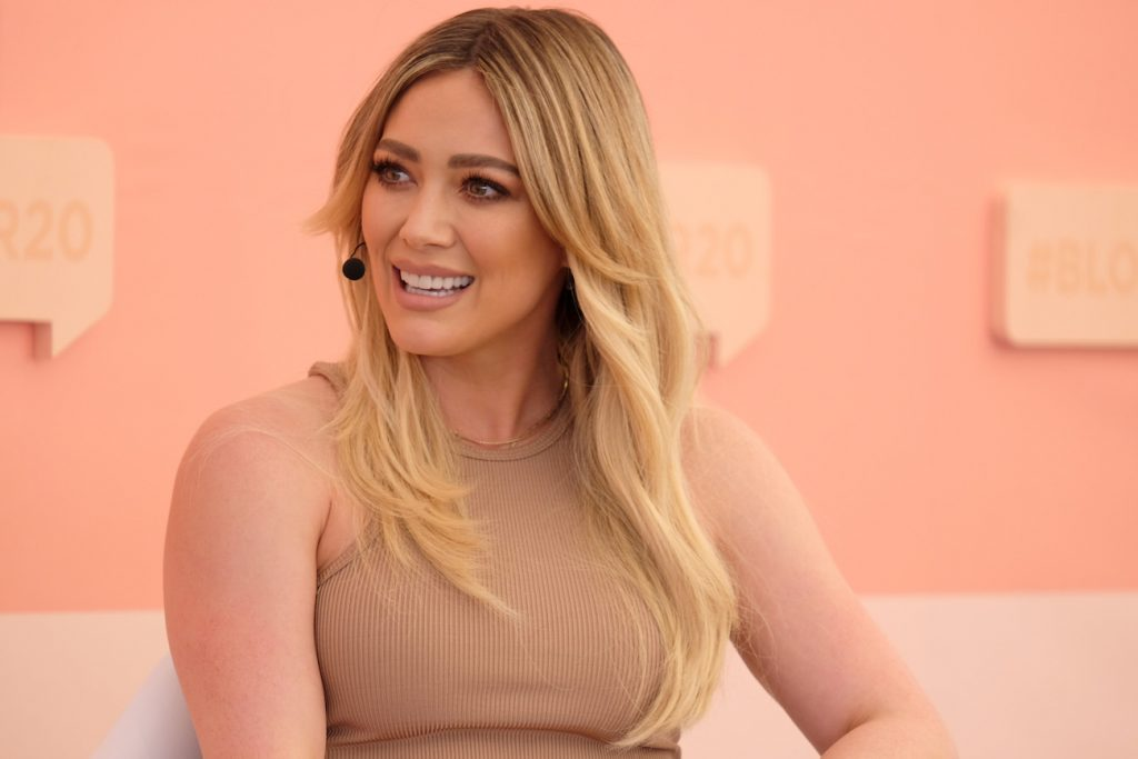 Hilary Duff sitting in front of beige background