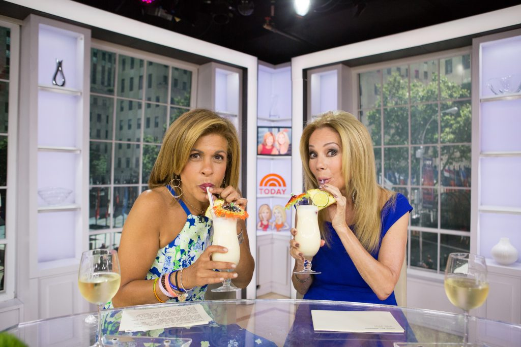 Hoda Kotb in a floral dress and Kathie Lee Gifford in a blue dress, both drinking from straws at the desk of 'Today with Kathie Lee & Hoda'