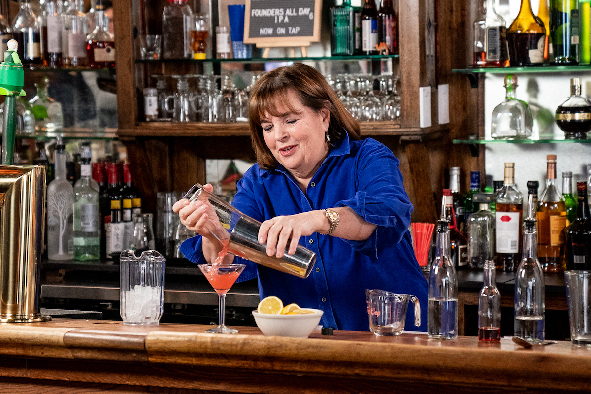 Ina Garten stands behind a bar and pours alcohol from a cocktail shaker into a martini glass on 'Late Night with Seth Meyers'