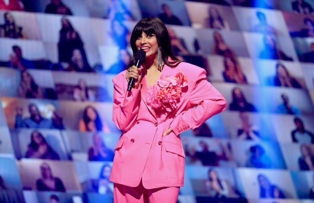 Jameela Jamil on stage in a pink suit and dangling earrings