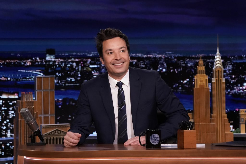 Jimmy Fallon smiling and sitting at his desk on 'The Tonight Show Starring Jimmy Fallon,' where he accrues an incredible net worth
