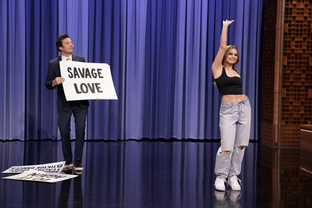 Addison Rae on the stage of 'The Tonight Show Starring Jimmy Fallon' with Jimmy Fallon in the background. Addison Rae's net worth is impressive thanks to her TikTok fame