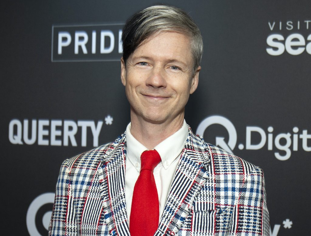 John Cameron Mitchell in a black, white, red, and blue suit, white shirt, and red tie in front of a grey background