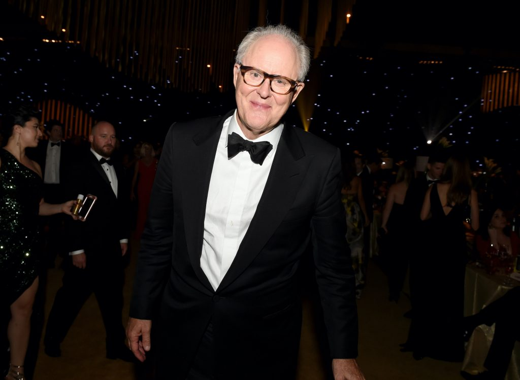 John Lithgow smiling in front of a theater full of people