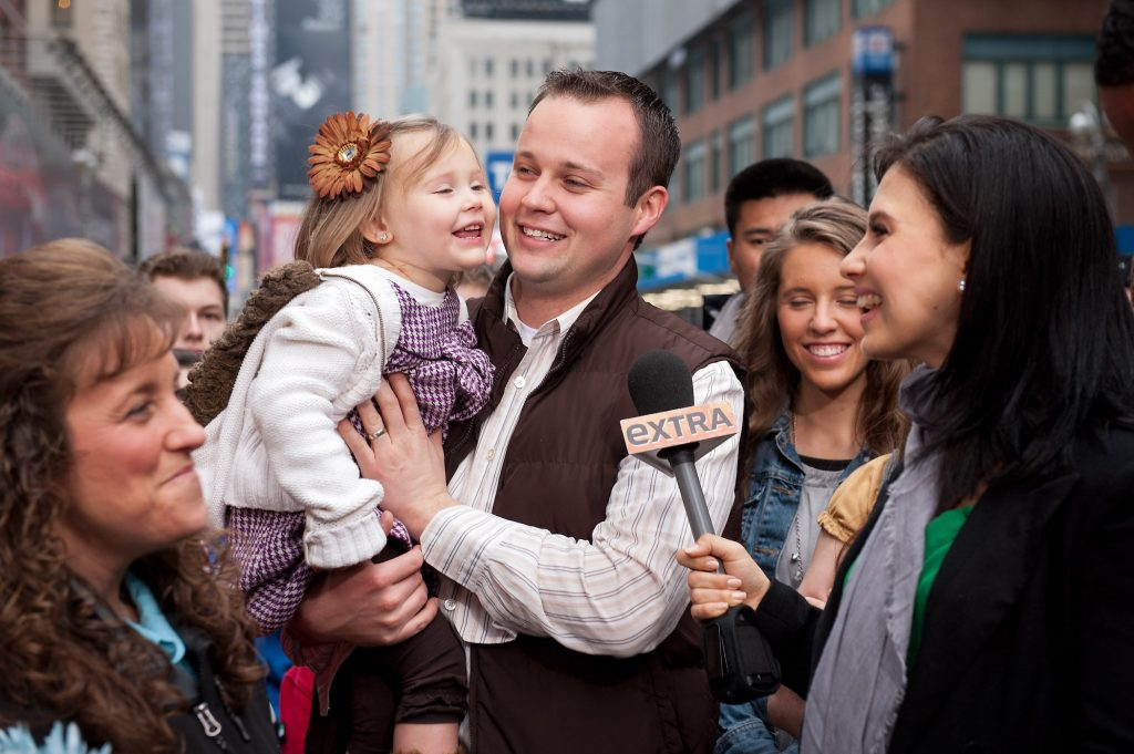 Josh Duggar and his daughter during their visit with 'Extra' surrounded by the rest of the Duggar family from 'Counting On'