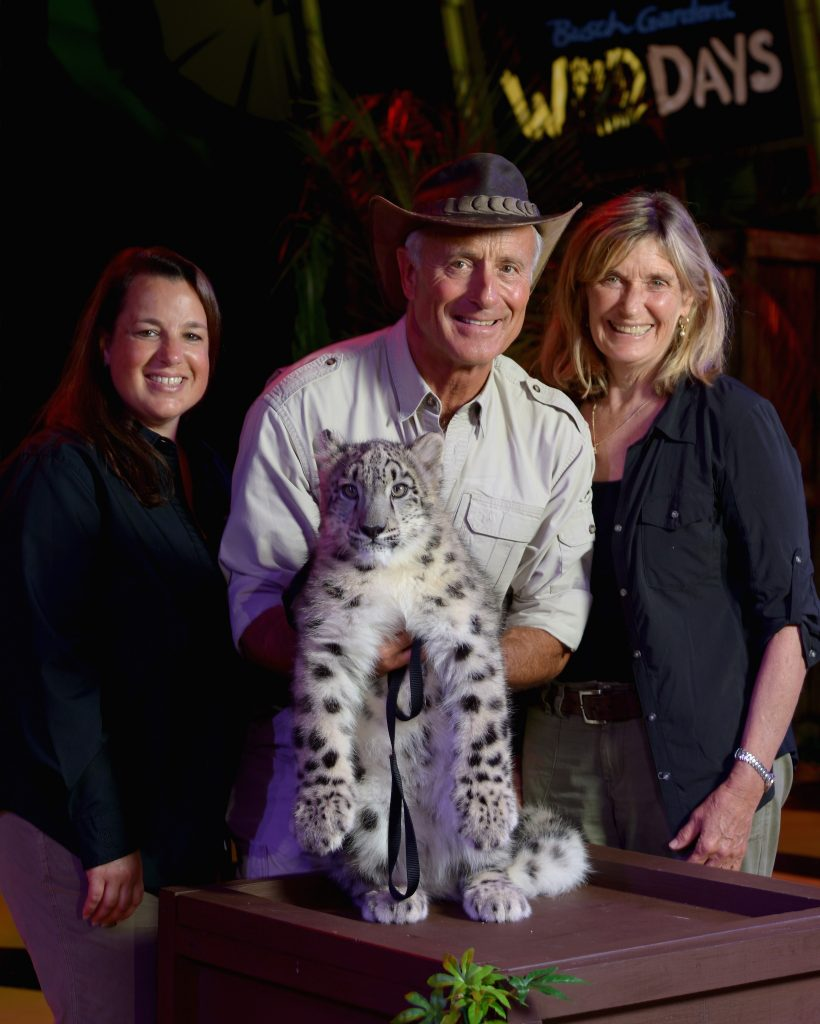 Jungle Jack Hanna standing with his wife and their daughter, Julie, as they pose with an endangered Snow Leopard