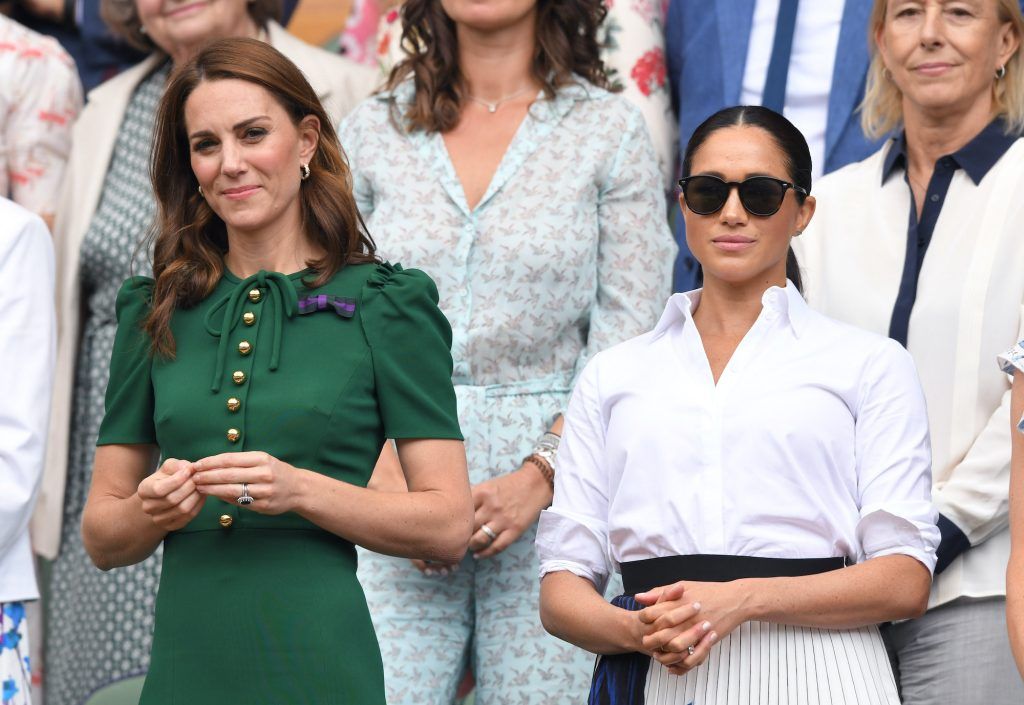 (L-R) Kate Middleton and Meghan Markle, standing in front of a crowd at a tennis match