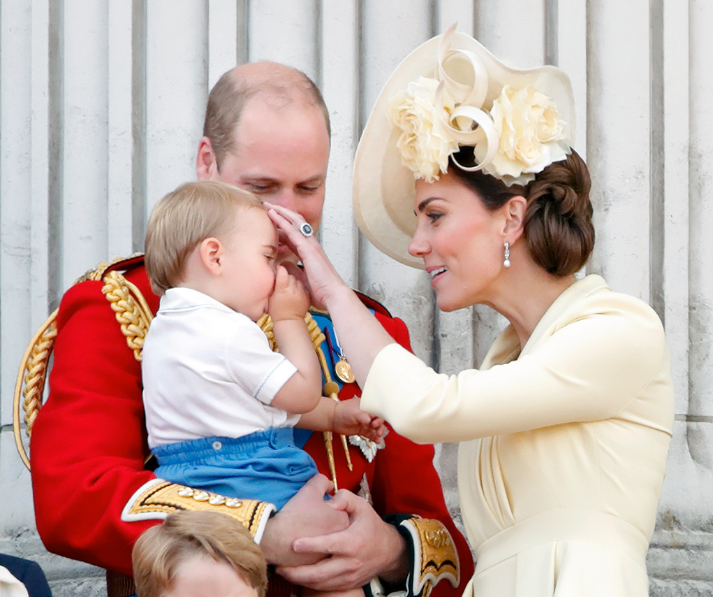 Kate Middleton gently touches Prince Louis' head as Prince William holds him on the Buckingham Palace balcony during Trooping the Colour