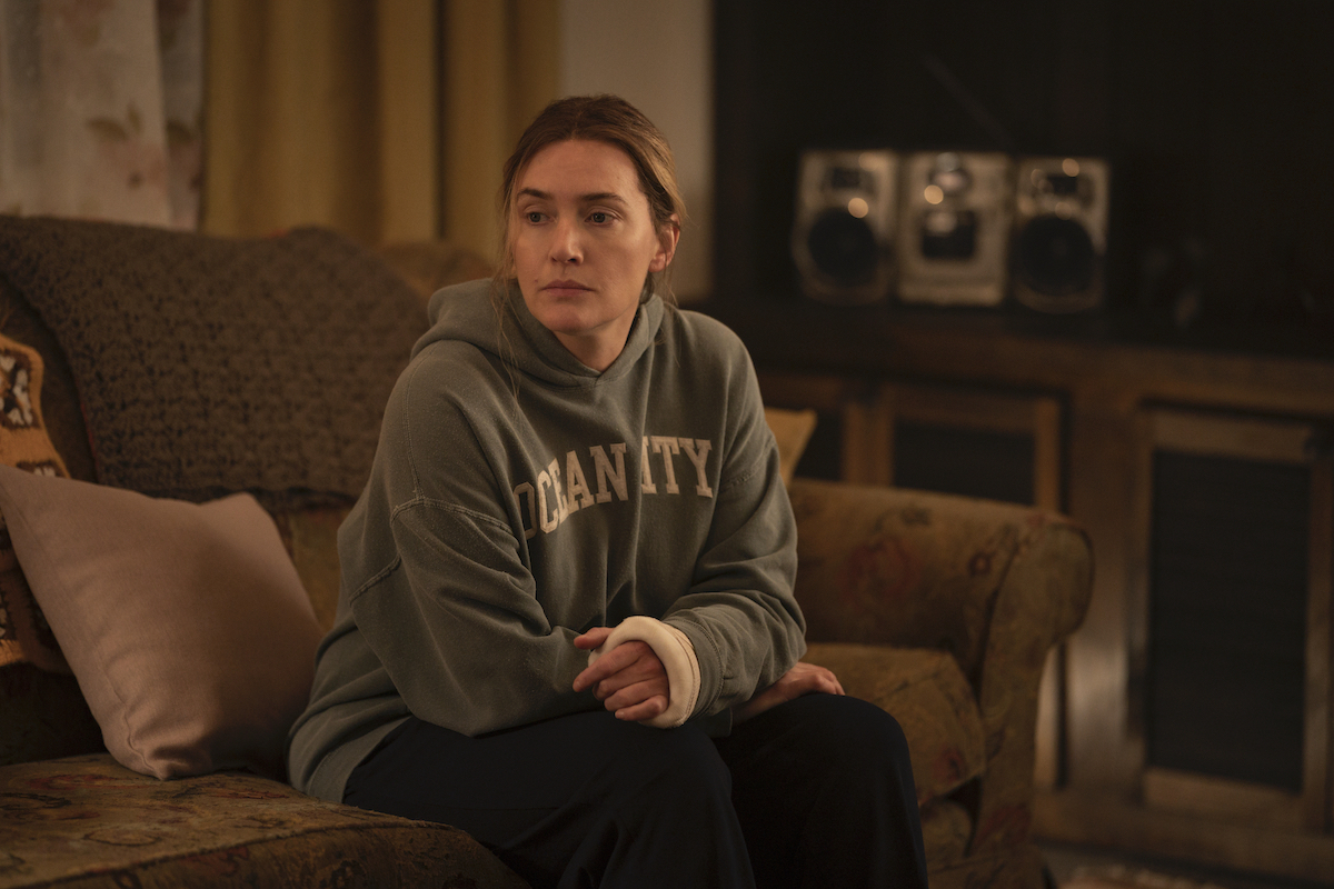 Kate Winslet sits on a couch wearing a hooded sweatshirt during a scene from 'Mare of Easttown'