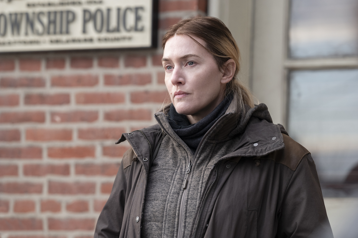 Kate Winslet stands outside of a brick building on 'Mare of Easttown'
