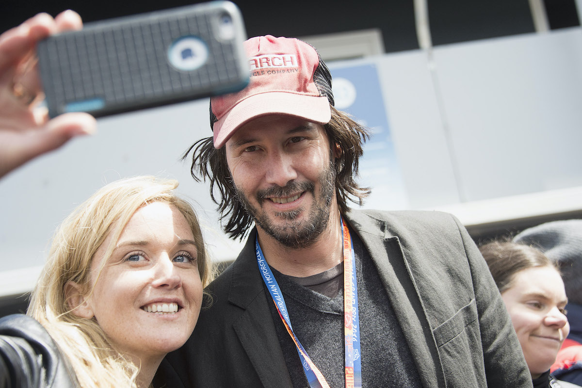 Keanu Reeves poses with a fan at the 2016 MotoGP of Australia at Phillip Island Grand Prix Circuit in Phillip Island, Australia