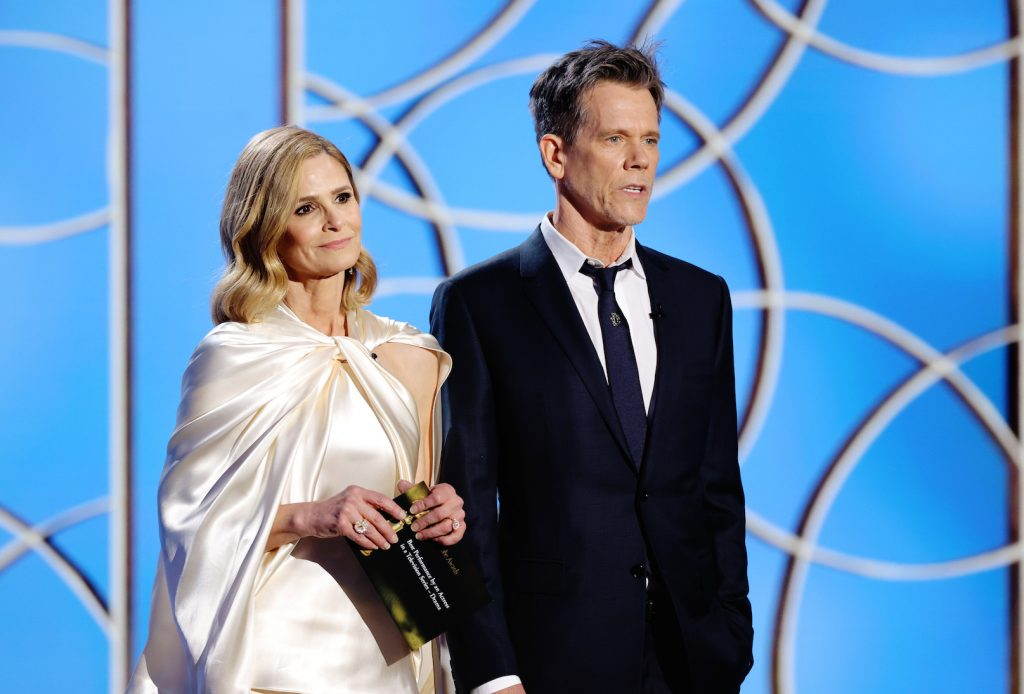Kyra Sedgwick and Kevin Bacon standing next to each other speaking onstage at the 78th Annual Golden Globe Awards