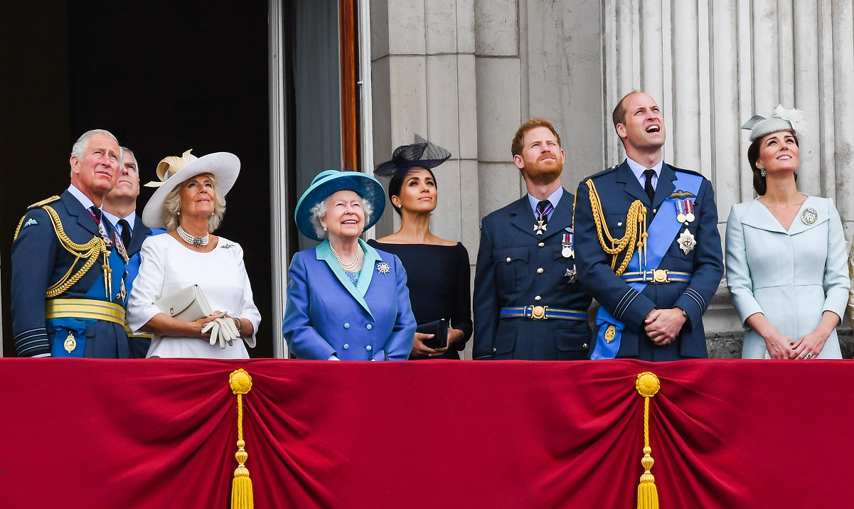 (L-R): Prince Charles, Camilla Parker Bowles, Prince Andrew, Queen Elizabeth ll, Meghan Markle, Prince Harry, Prince William, and Kate Middleton standing on the balcony of Buckingham Palace watching a flypast