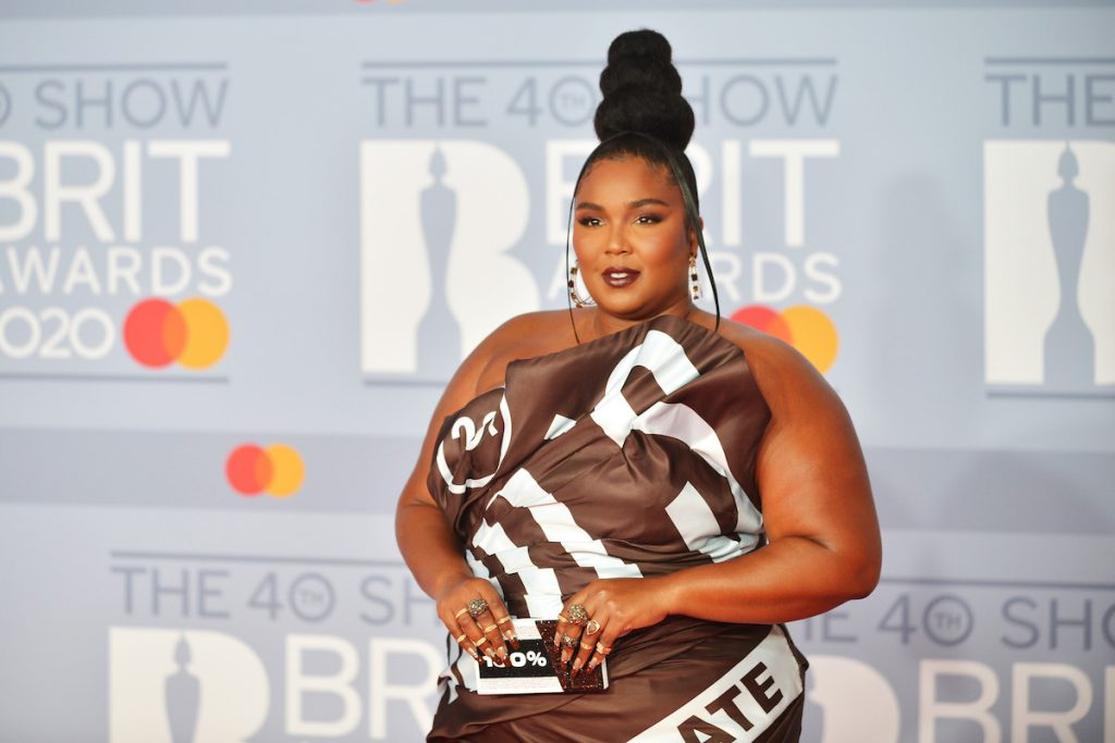 Lizzo in a brown dress and rings