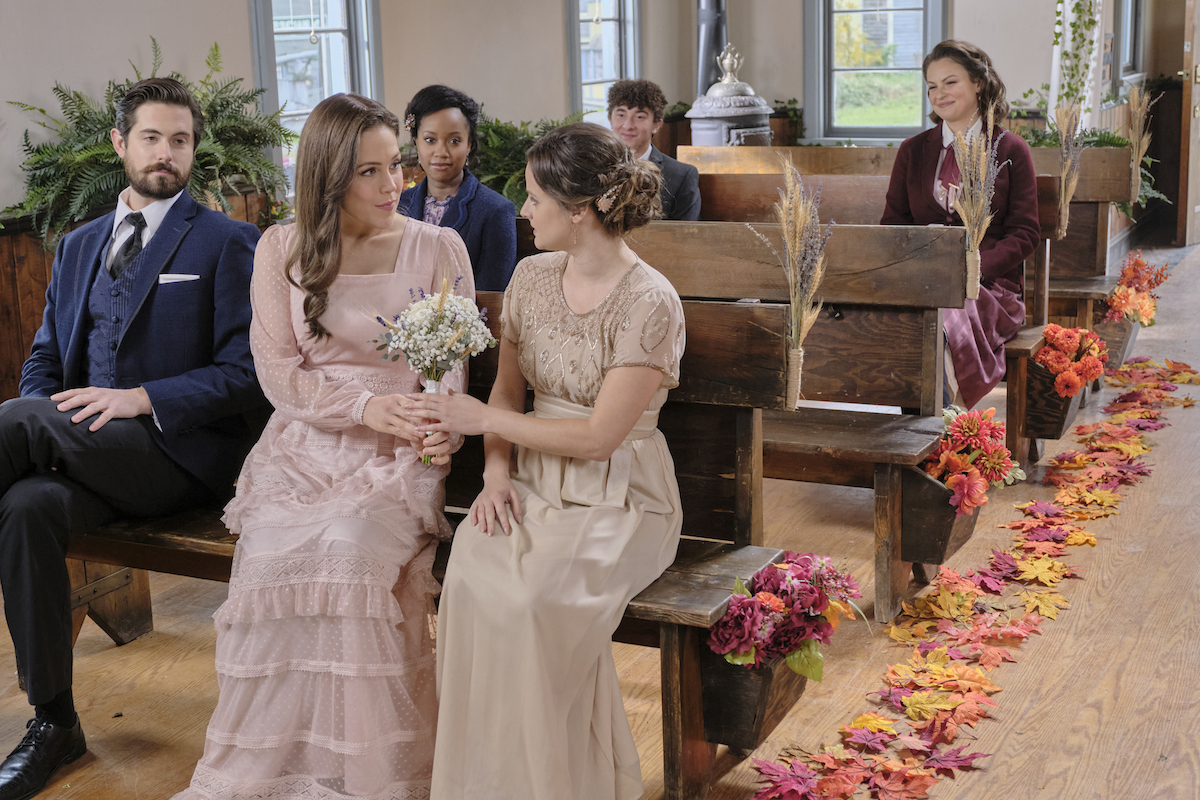 Lucas, Elizabeth, and Kate sitting on a pew in church in episode of When Calls the Heart