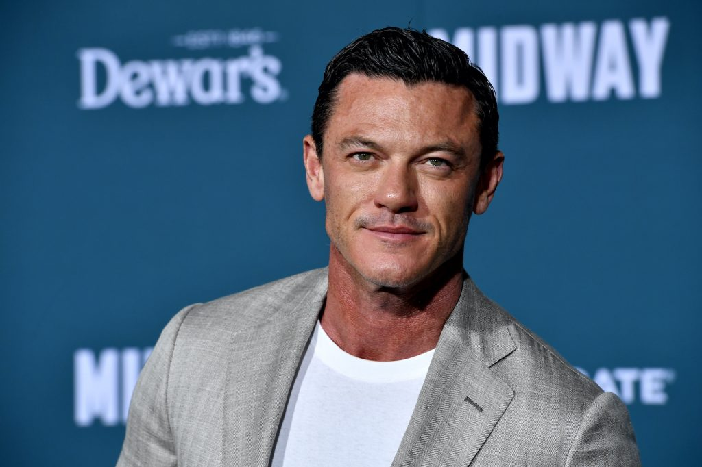 Luke Evans smiling in front of a blue background