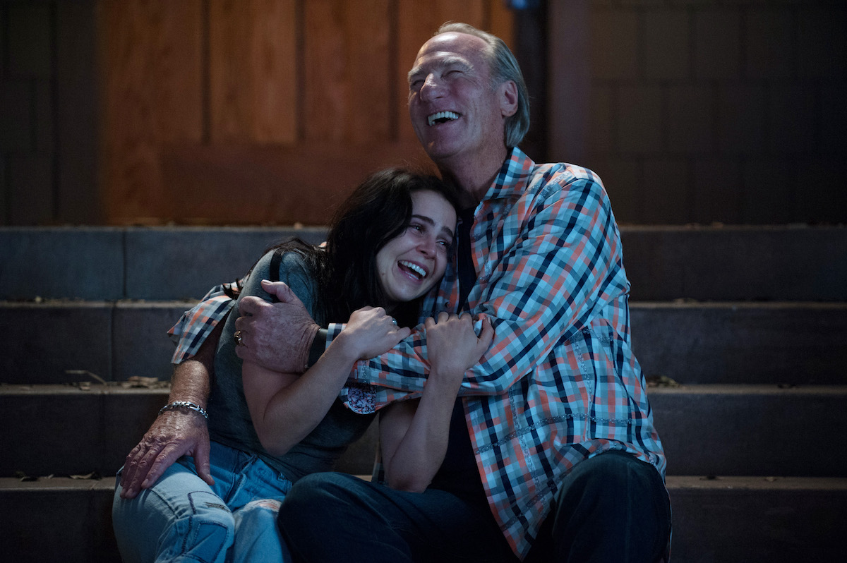 Mae Whitman and Craig T. Nelson embrace while sitting on a set of stairs during a scene on 'Parenthood'