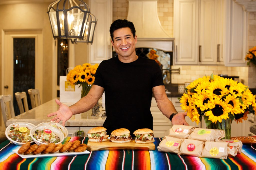 Mario Lopez of 'Access Hollywood' stands in front of items from his menu at Mario's Tortas Lopez