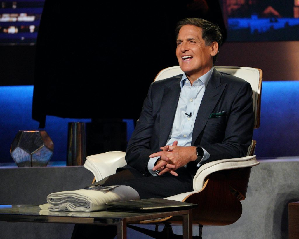 Mark Cuban smiling in a dark jacket on the panel of 'Shark Tank'