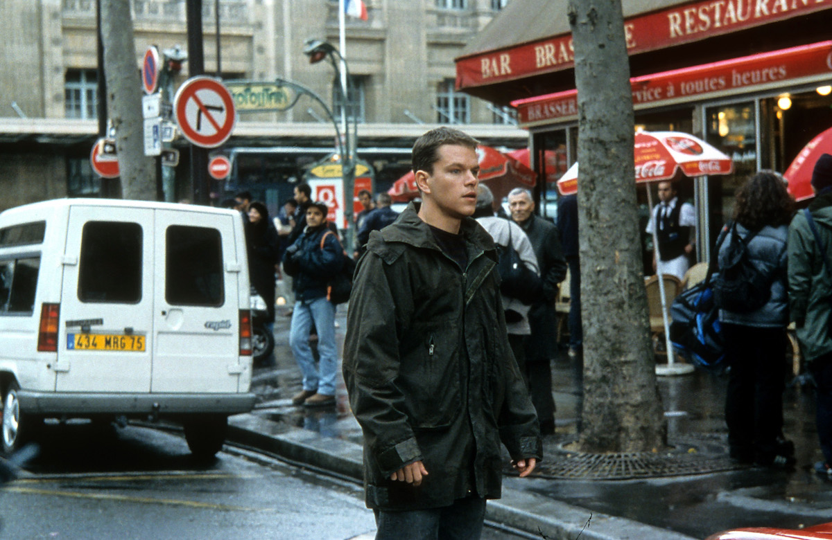 Matt Damon stands in the street while people stand on the sidewalk during the filming of 'The Bourne Identity'