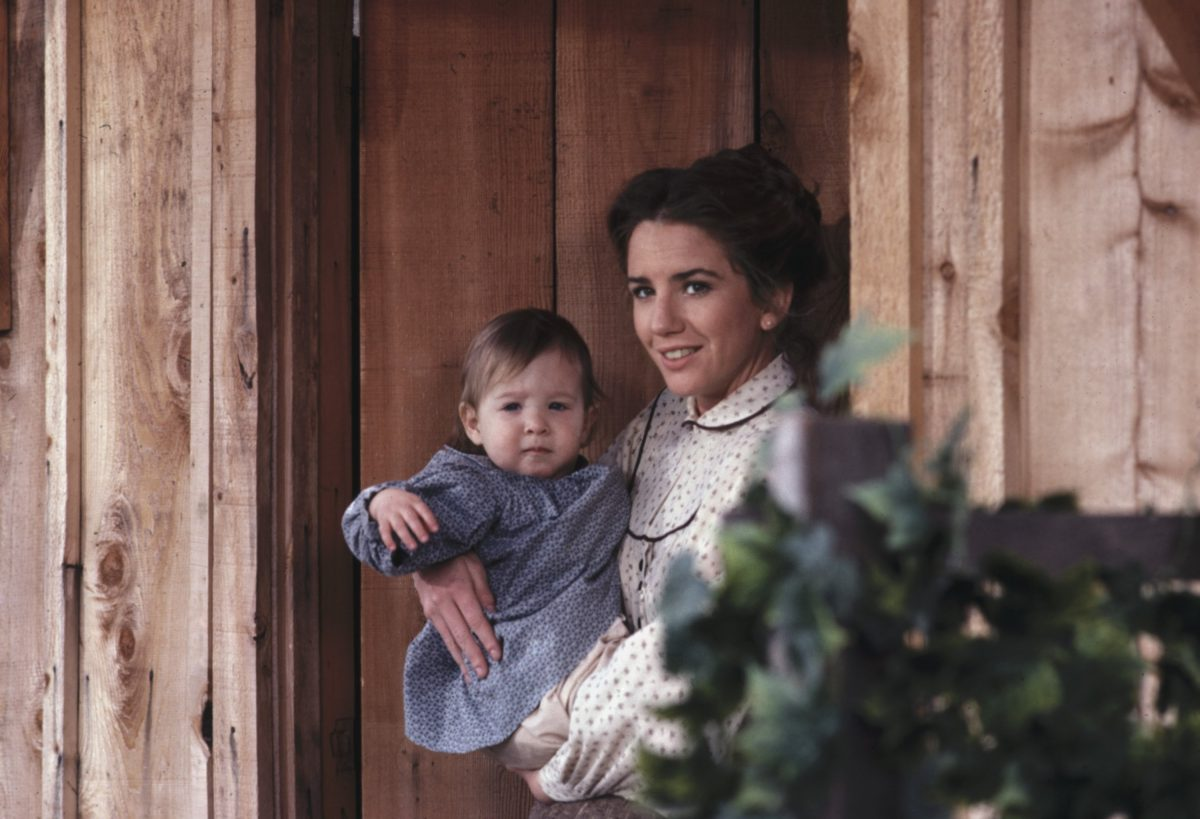 Melissa Gilbert as Laura Ingalls Wilder, holding her baby, on the set of 'Little House on the Prairie.'