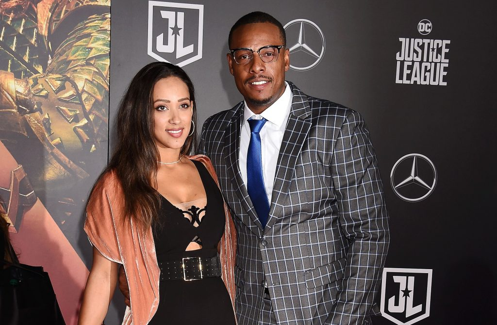 Former NBA player Paul Pierce in patterned suit and his wife, Julie Landrum, in a black dress posing on red carpet at movie premiere