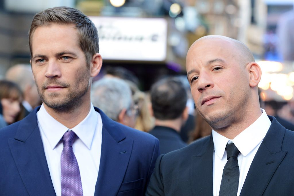 Paul Walker and Vin Diesel are wearing suits on a red carpet
