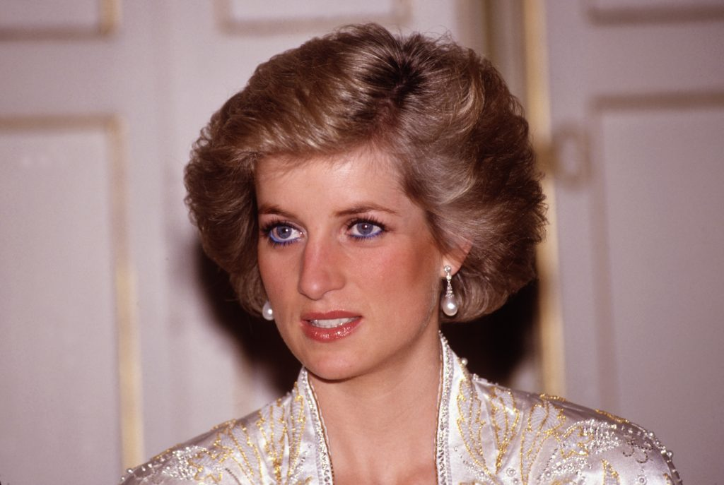 Photo of Princess Diana from the shoulders up wearing pearl-drop earrings and her signature blue eyeliner