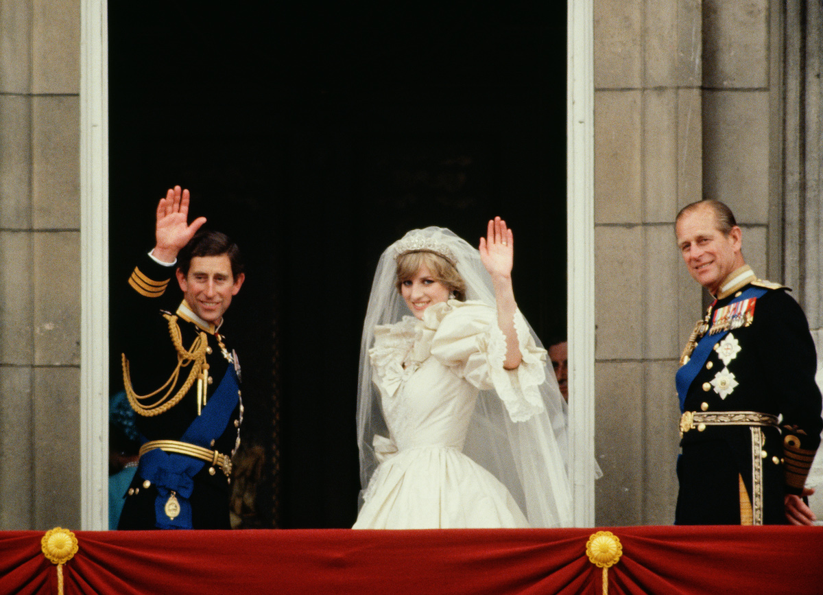 Prince Charles and Princess Diana wave from the balcony of Buckingham Palace following their royal wedding as Prince Philip stands next to them royal wedding