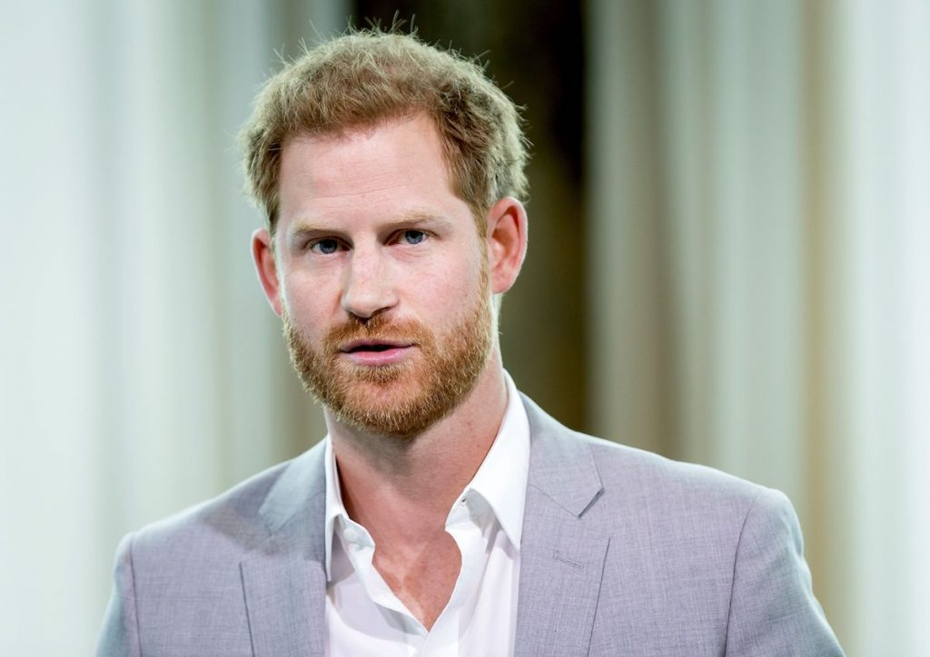 Prince Harry looks into the camera wearing a white shirt and grey blazer