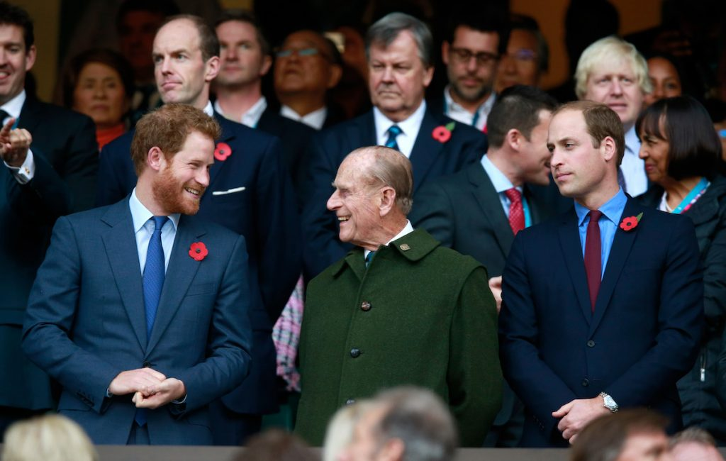 Prince Harry and Prince Philip smiling at each other as Prince William looks on.