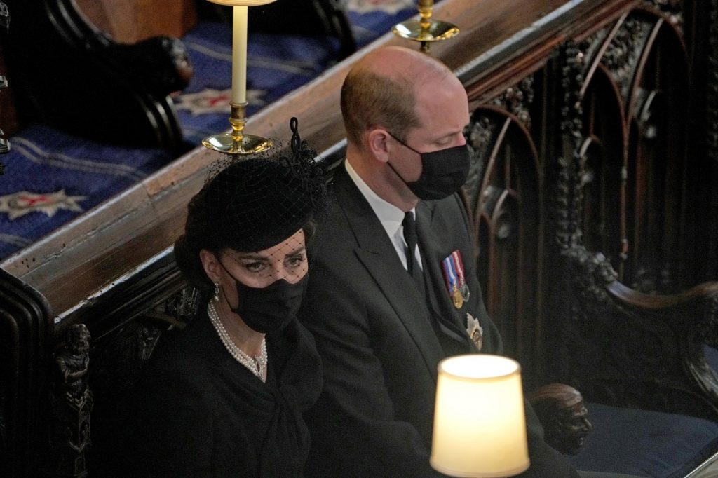 Prince William and Kate Middleton sitting next to each other in church during  Prince Philip's funeral service