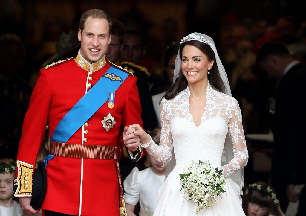 Prince William and Kate Middleton smiling and holding hands following nuptials at Westminster Abbey on April 29, 2011
