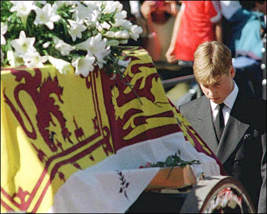 Prince William walks with his head bowed behind the coffin of his mother