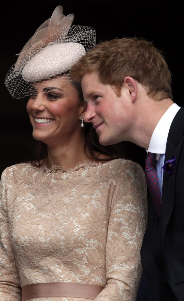 Prince leaning over Kate Middleton's shoulder to get in a photo