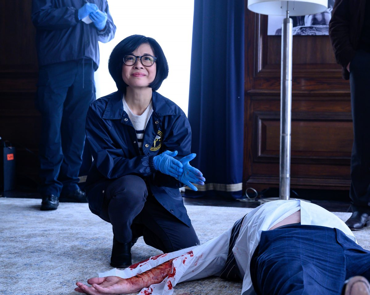 """Kieko Agena kneels next to a victim in """"Wait and Hope"""", the 13th episode of 'Prodigal Son'"""