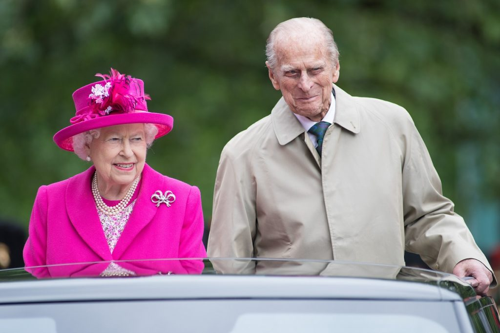 Queen Elizabeth II dressed in a bright pink outfit and hat next to Prince Philip smiling in a light-colored coat