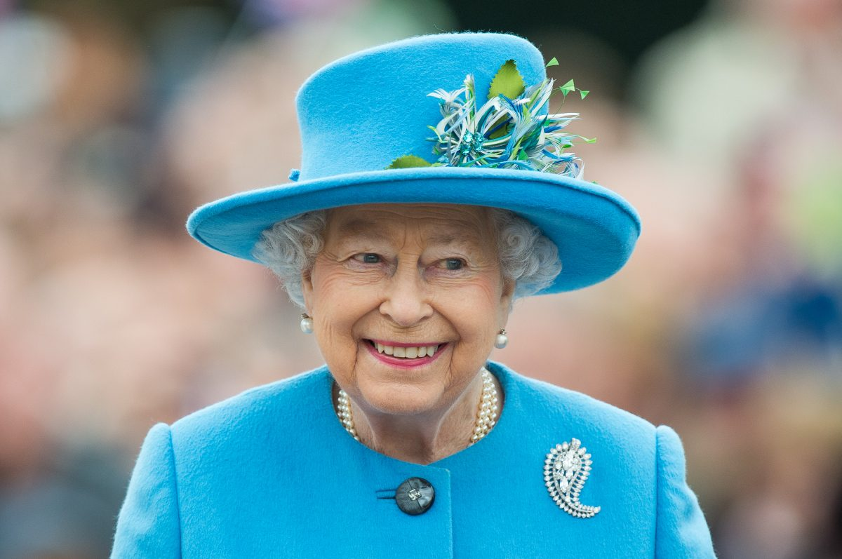 Queen Elizabeth II smiling during tour of Queen Mother's Square dressed in a baby blue hat and matching blazer