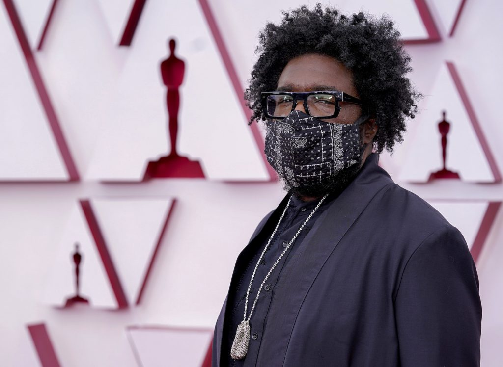 Questlove, one of the best dressed at the Oscars in 2021, wearing a mask and a black suit with a gold chain on the red carpet