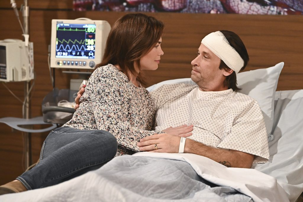 Rebecca Herbst and Roger Howarth lying on hospital bed in a still from General Hospital