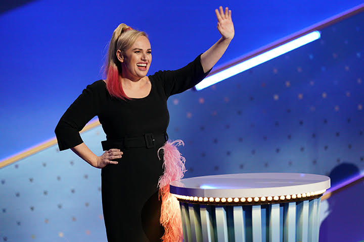 Rebel Wilson stars as host of 'Pooch Perfect', coming on stage waving in a black dressa