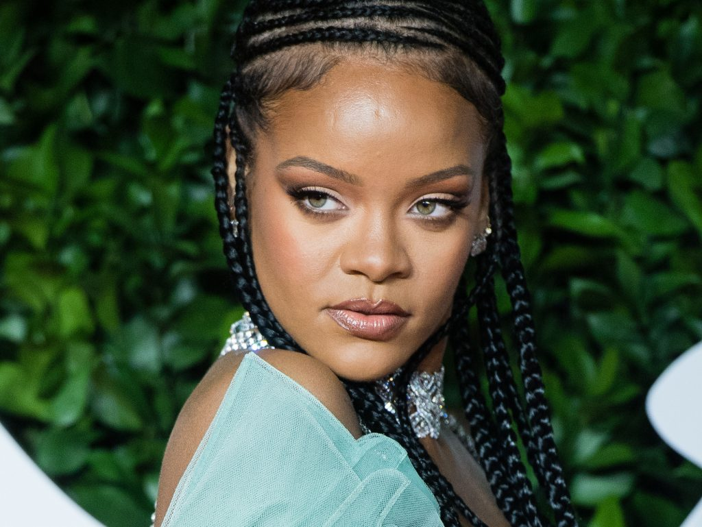 Rihanna in front of a green background