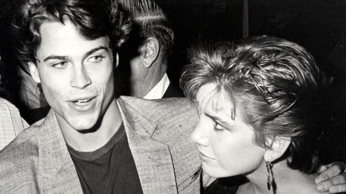Rob Lowe and Melissa Gilbert in black and white. Lowe has his arm around Gilbert, and she's looking at him while he speaks.