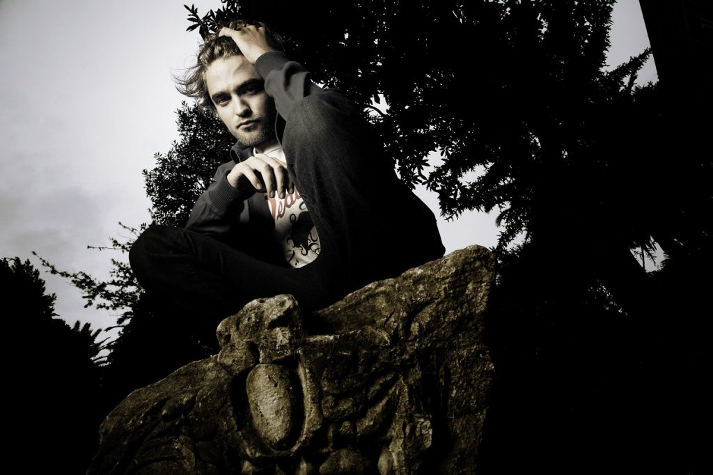 Twilight movies star Robert Pattinson squats with a hand in his hair as he poses for cast portraits