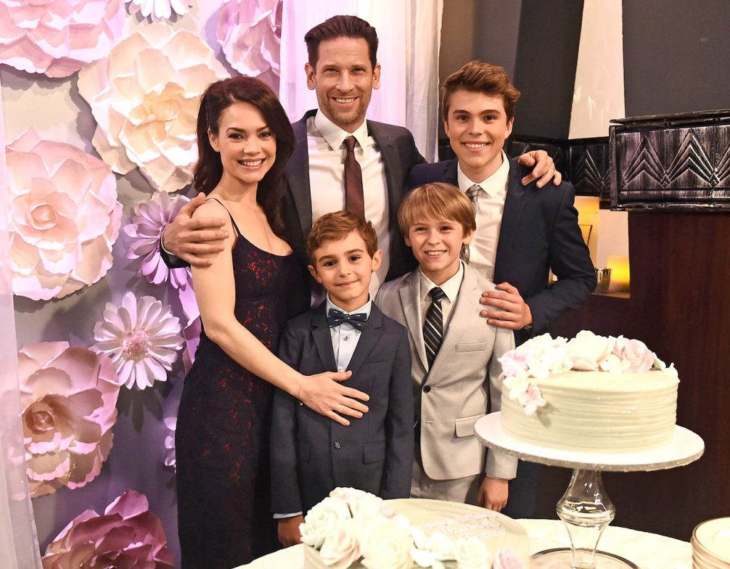 Rebecca Herbst, Roger Howarth, and their on-screen kids in a still from General Hospital