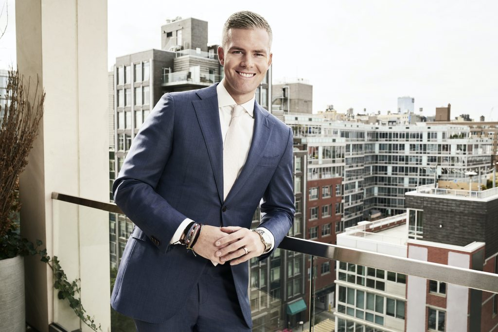 Ryan Serhant smiling in front of a cityscape