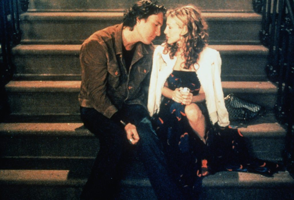 John Corbett as Aidan Shaw and Sarah Jessica Parker as Carrie Bradshaw sit on the steps of her New York City brownstone during the filming of 'Sex and the City'