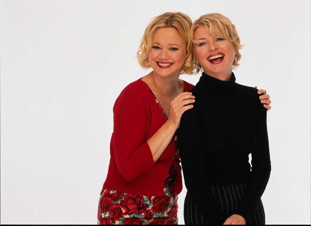 Caroline Rhea and Beth Broderick smiling in front of a white background