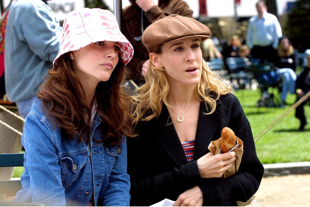 Kristin Davis as Charlotte York and Sarah Jessica Parker as Carrie Bradshsaw sitting on a bench in Central Park during a scene for 'Sex and the City' in 2001